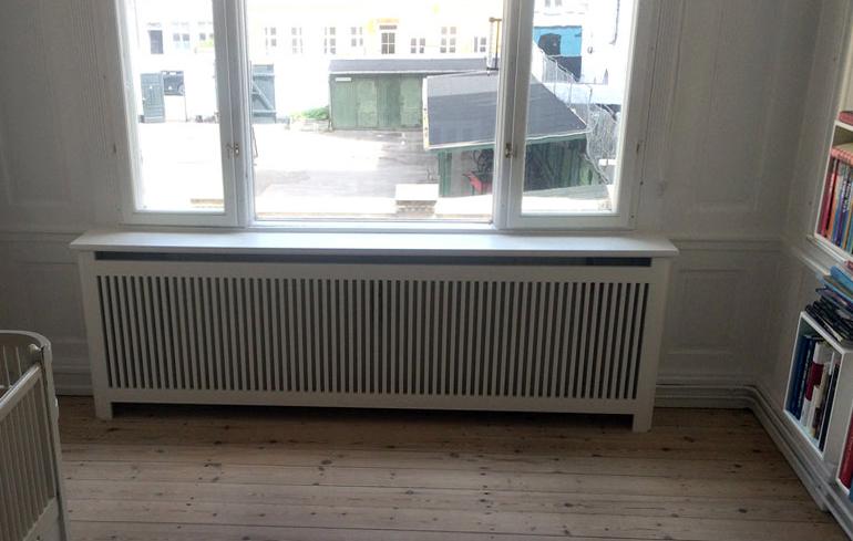 Smuk hvid radiatorskjuler som flugter flot med vægpanelerne. Radiatorskjuleren fungerer også som vindueskarm.