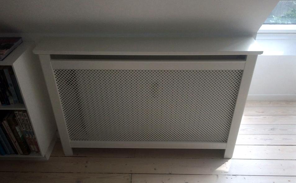 Klassisk hvid radiatorskjuler med kløver mønsterplade.