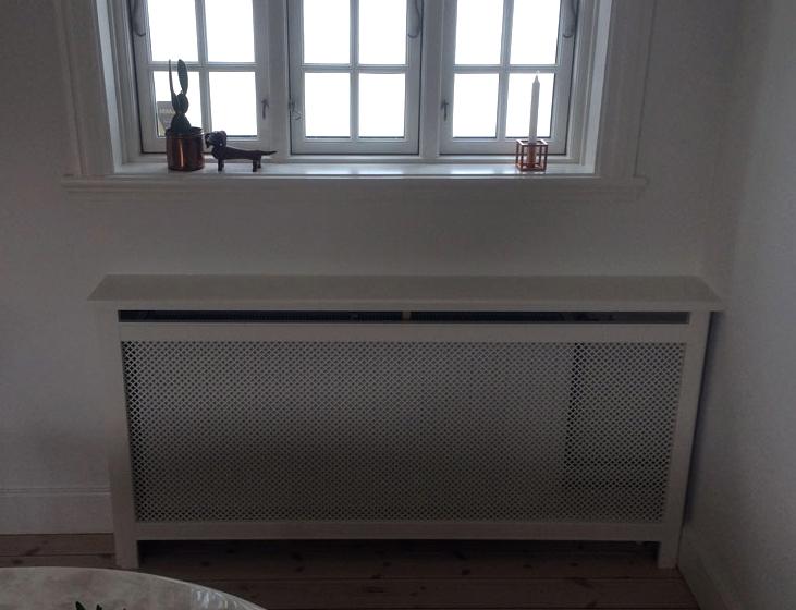 En radiator kan ikke fungere som et integreret møbel i stuen, men det kan en radiatorskjuler. Denne har en fin afsætningsplads til stuens blomster.