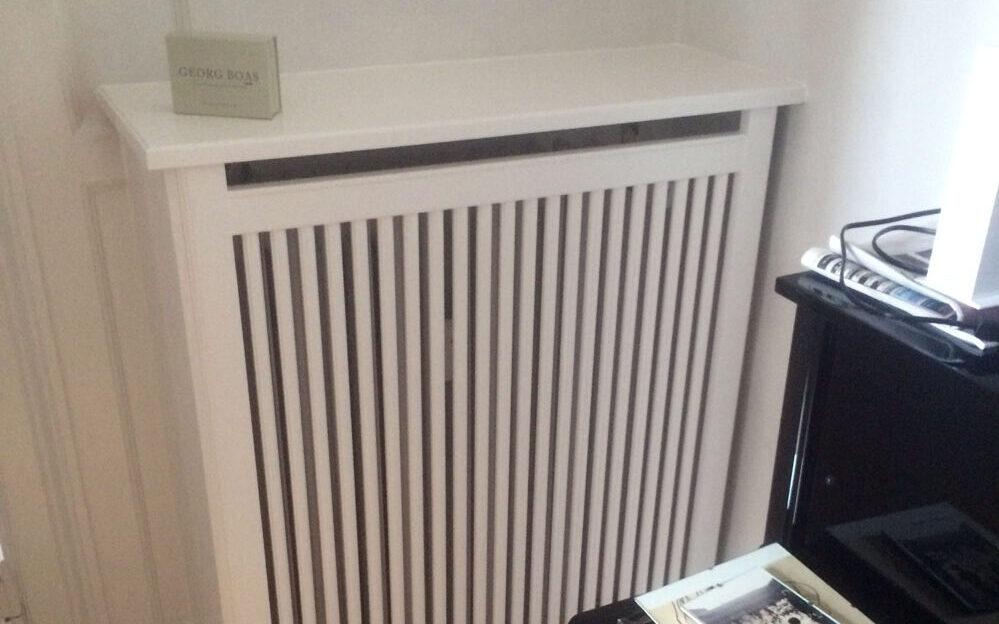 Høj hvid radiatorskjuler med bentypen Trørød.