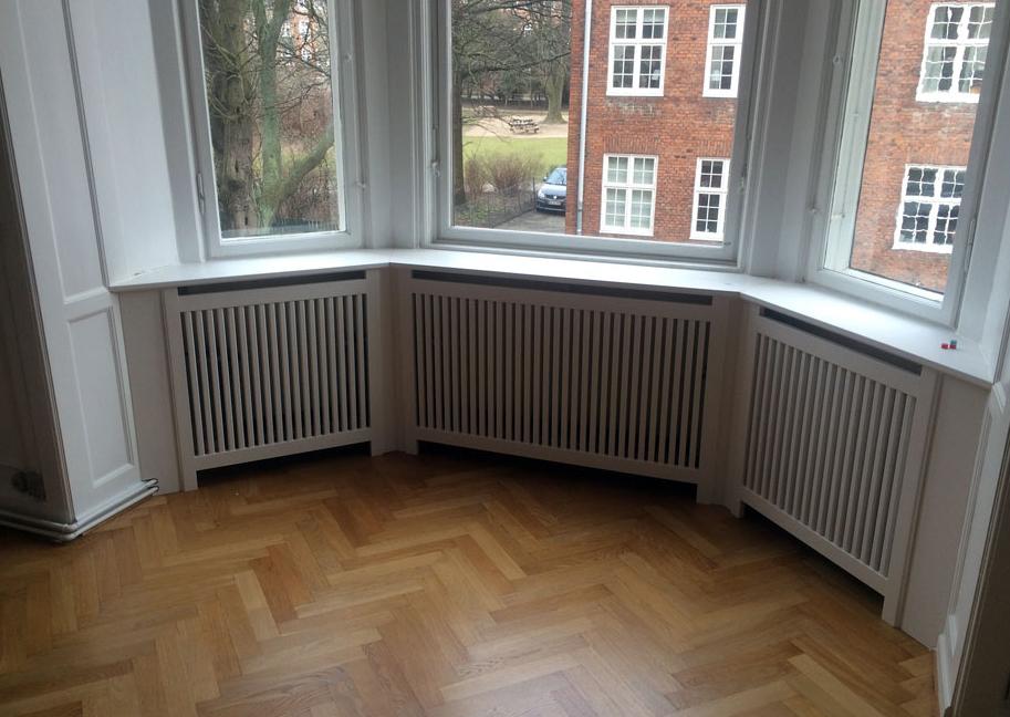 Hvid specieldesignet radiatorskjuler med vinkler og vindueskarm.