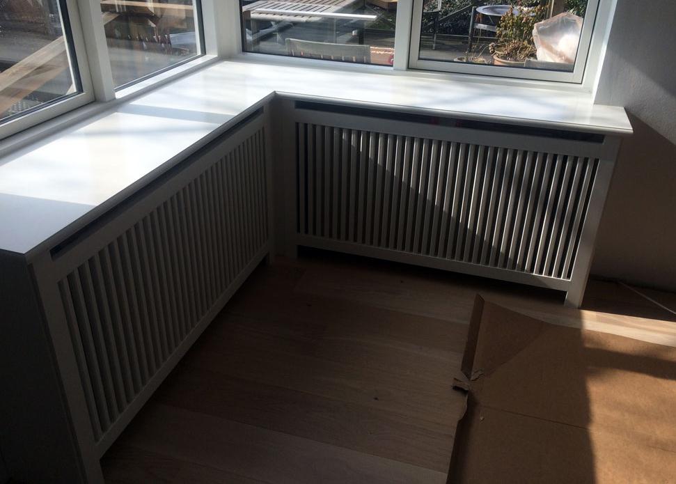 Hvis stilren radiatorskjuler. Denne skjuler er en hjørneskjuler, som også fungerer som vindueskarm.