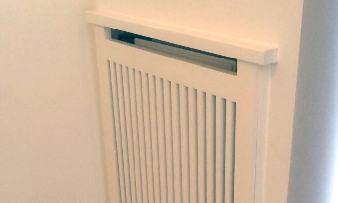 Indbygget radiatorskjuler med Gentofte trætremmer. Vægkunst når det er bedst.