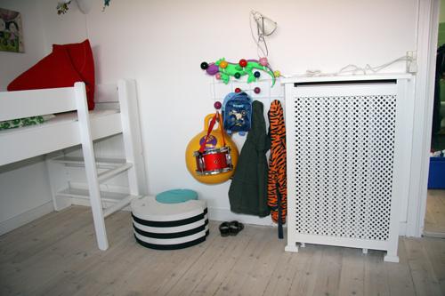 Radiatorskjuler på børneværelset med antikke ben og en flot mønsterplade.