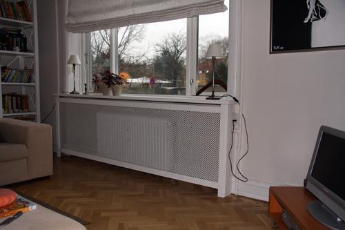 Radiatorskjuler under vindue med kløver mønsterplade og Trørød ben.