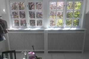 Under vindue står radiatorskjuler med gentofte trætremmer og trørød ben