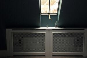 Radiatorskjuler med D'angleterre mønsterplade og særlige trørød ben under vindue