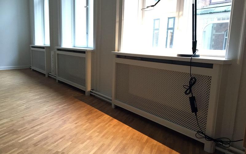 Radiatorskjuler med Kløver mønsterpladde og trørød ben under vindue
