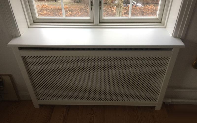 Radiatorskjuler med antikflet mønsterpladde og trørød ben under vindue