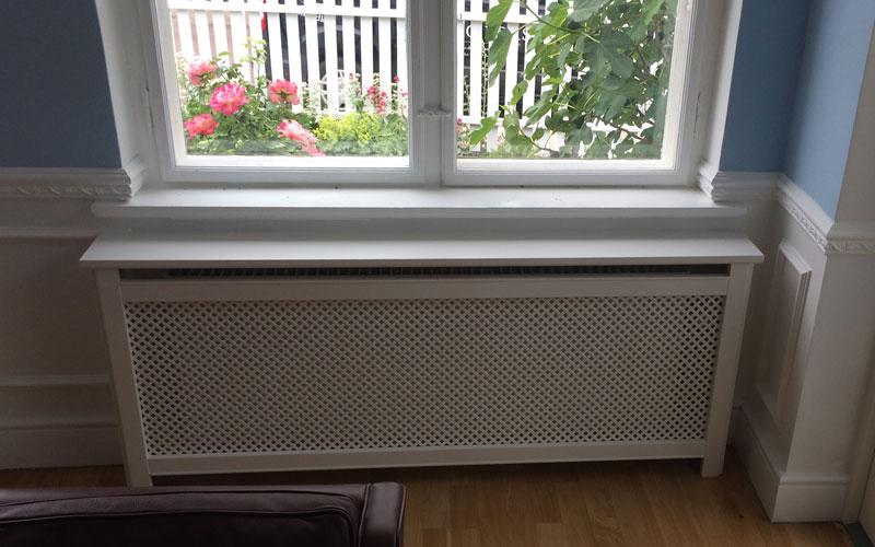 Antikflet mønsterplade og trørød ben på radiatorskjuler under vindue