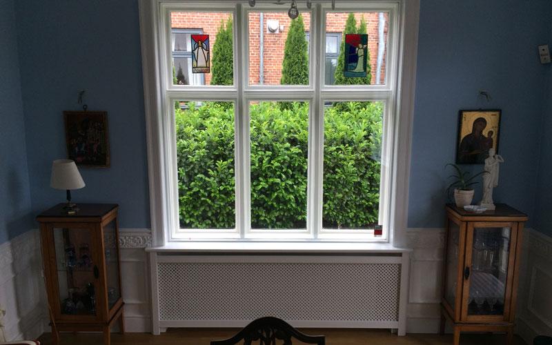 Antikflet mønsterplade med trørød ben på radiatorskjuler under vindue
