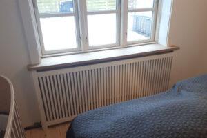 Radiatorskjuler under vindue med gentofte trætremmer og trørød ben