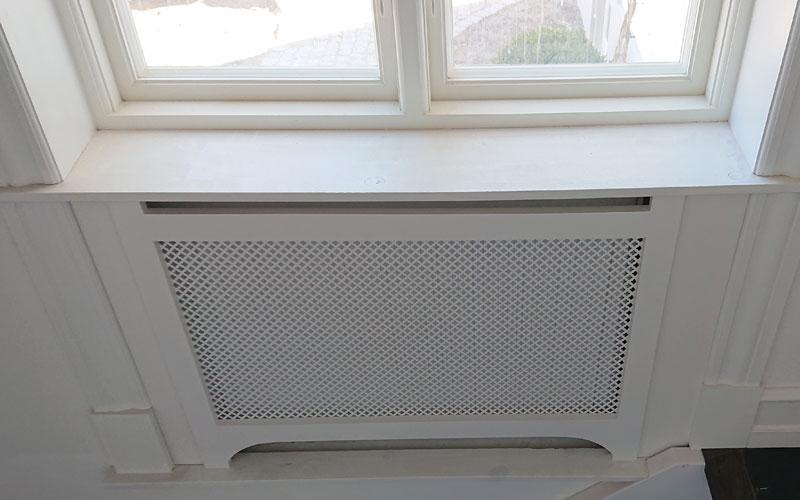 Radiatorskjuler under vindue med stjerne mønsterplade og gentoft ben