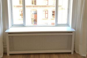 Radiatorskjuler under vindue med kløver mønsterplade og trørød ben