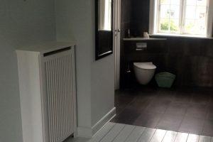 Et gammelt hus med moderne stil kræver en moderne radiatorløsning. Hvid radiatorskjuler med trætremmer.