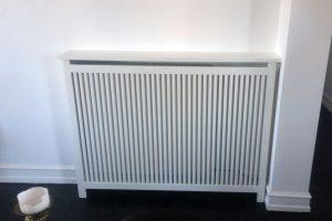 Få radiatoren til at indgå naturligt i din indretning med en radiatorskjuler. Her Gentofte trætremmer.
