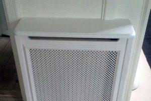 Flot hvid radiatorskjuler med afrundede hjørner mellem to døråbninger.