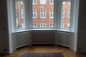 Hvid radiatorskjuler med trætremmer. Skjuleren flugter med boligen flotte paneler.