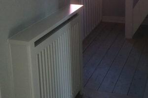 Hvid radiatorskjuler på rapos. Skjuleren fremstår som en naturlig del af boligen i forlængelse med fodpanelen.