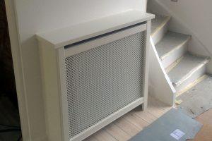 Hvid radiatorskjuler ved et indgangsparti. Her er mulighed for at pynte med en vase eller en skål med nøgler. Skjuleren er prydet med en kløver mønsterplade.